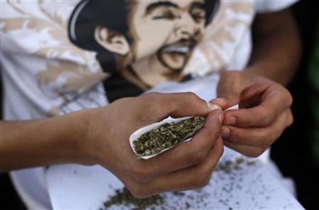 A man rolls a joint during the 4th Marijuana Festival outside the Senate building in Mexico City